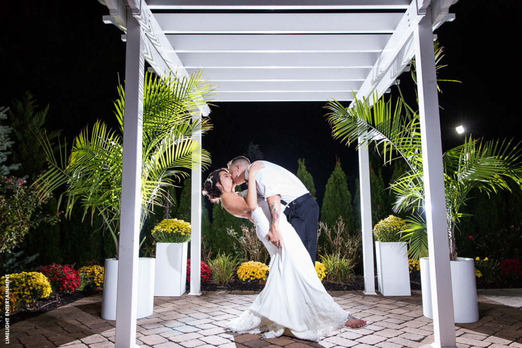 Bride and groom stealing a kiss under the pergola at the Sterling Ballroom.